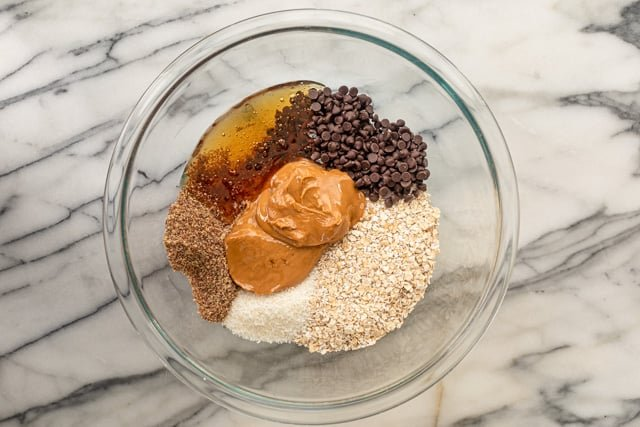 Ingredients in a bowl: oats, peanut butter, chocolate, honey, flaxseed, coconut