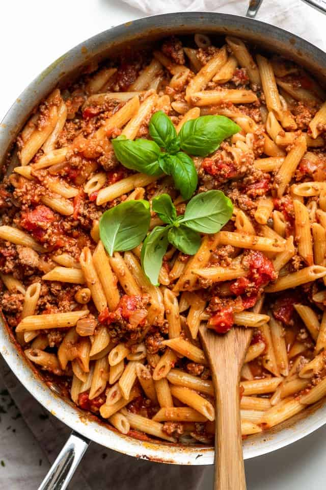 Pasta Bolognese in a large pan topped with fresh basil leaves with a wooden spoon