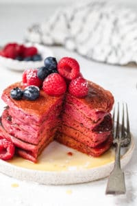 Stack of pink pancakes cut with fork on the side