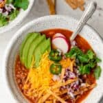 Close up shot of vegetarian tortilla soup with all the toppings