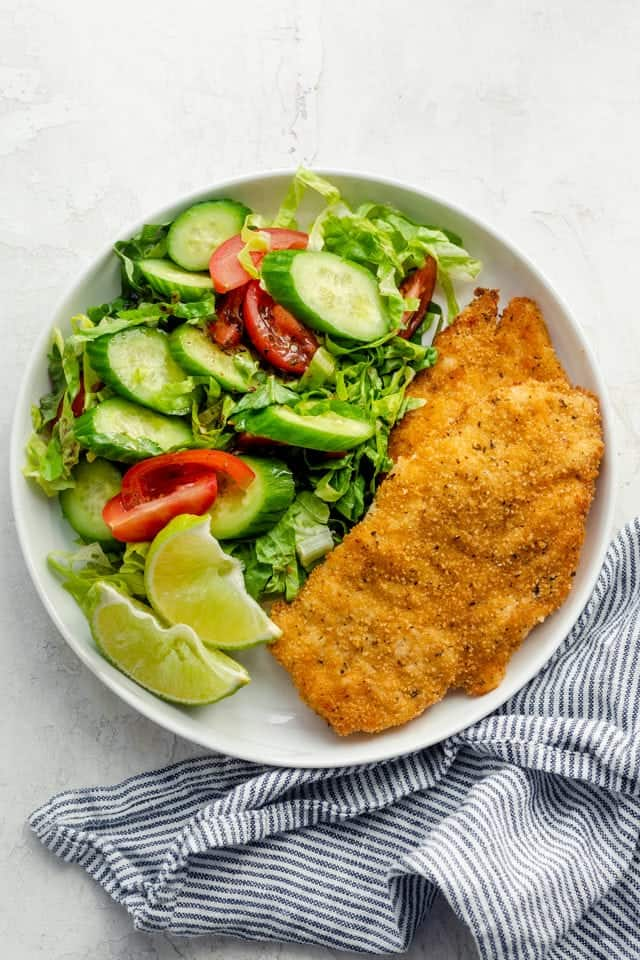 Plated breaded air fryer chicken breasts served with a side salad