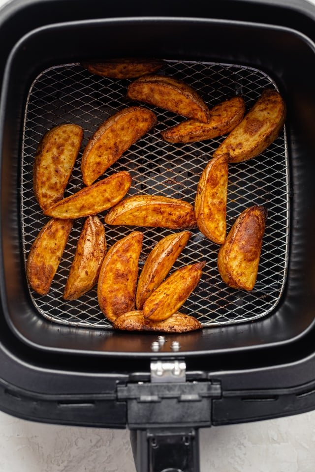 Potato wedges in the air fryer after they're finished cooking