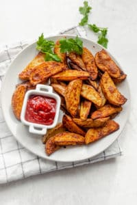 Large plate of air fryer potatoes sered with ketchup