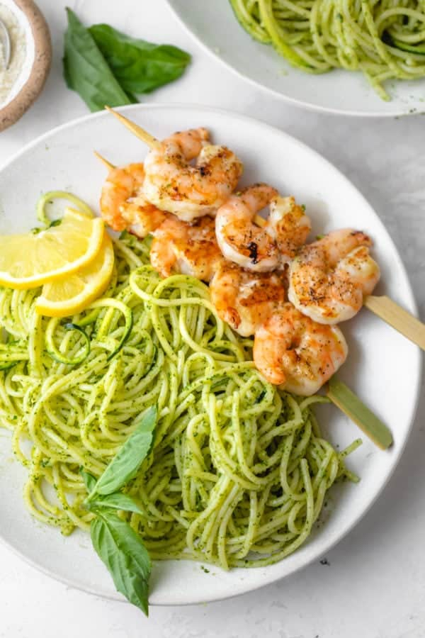 Plate of pesto spaghetti with grilled shrimp on the side