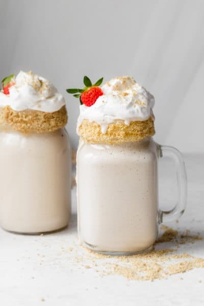 Final tahini milkshake recipe with cool whip, and strawberries and cookie frosted glasses