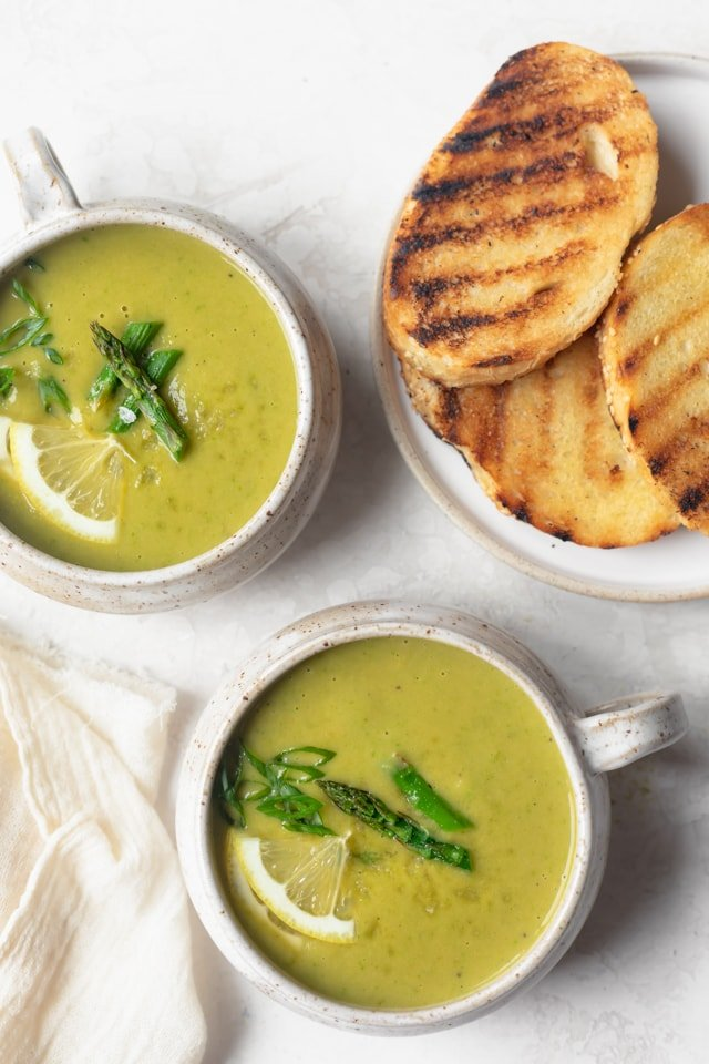 Final vegan asparagus soup in soup mugs served with grilled bread