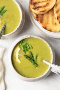 Close up of cream of asparagus soup in bowl with spoon