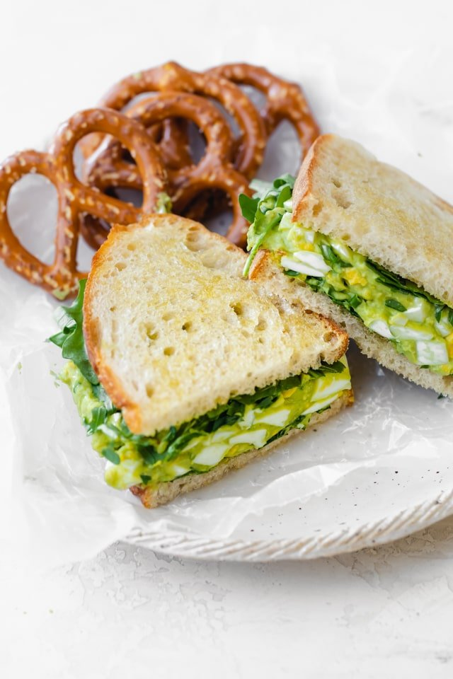 Avocado egg salad sandwich with pretzels on a white plate