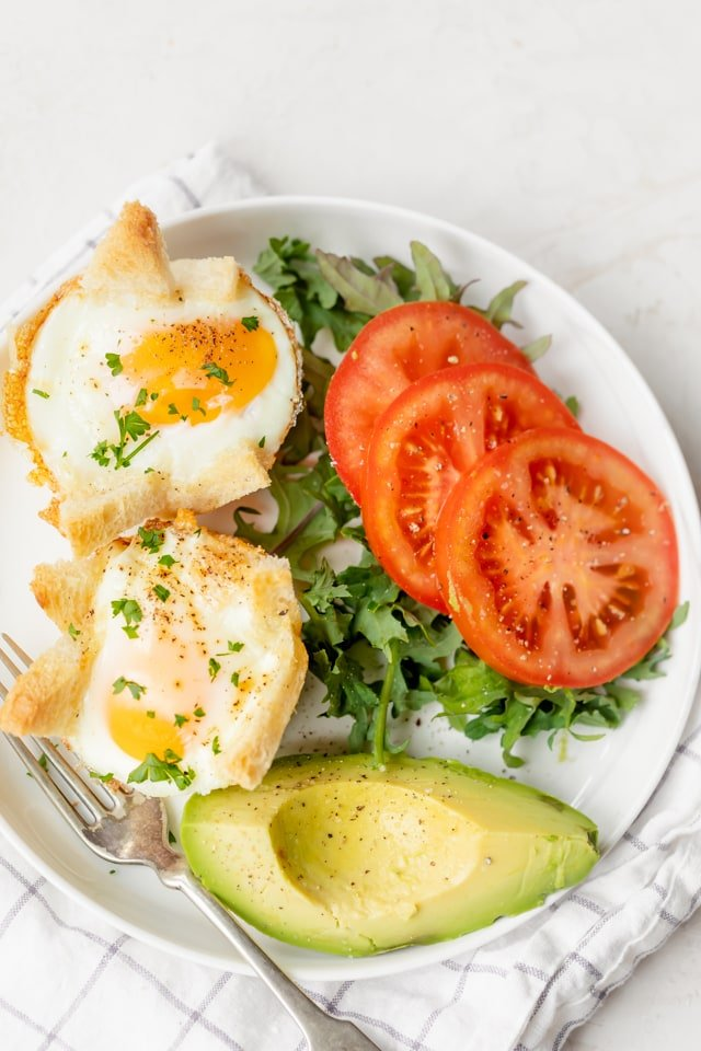 Two baked eggs in bread served with tomatoes and avocado