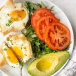 Cutting into eggs on a plate with tomatoes and vocado
