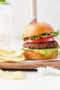 Final recipe showing the salsa black bean burger in a bun with condiments next to potato chips