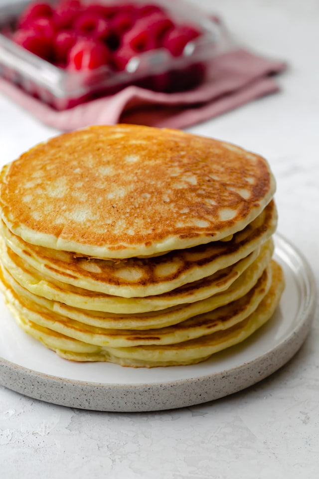 Stack of lemon ricotta pancakes on a white plate with raspberries in the background