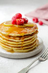 Stack of lemon ricotta pancakes with maple syrup drizzling down the sides and topped with raspberries