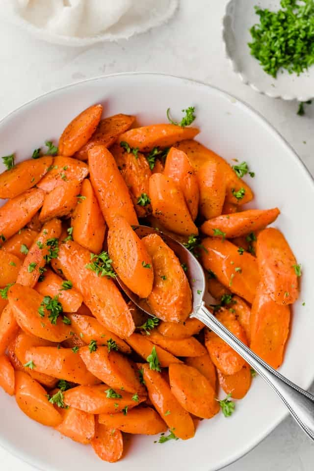 Large bowl of oven roasted carrots sprinkled with parsley