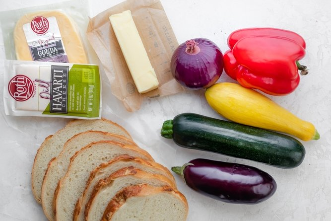 Ingredients to make grilled cheese sandwich - bread, Roth cheese, butter and assorted vegetables