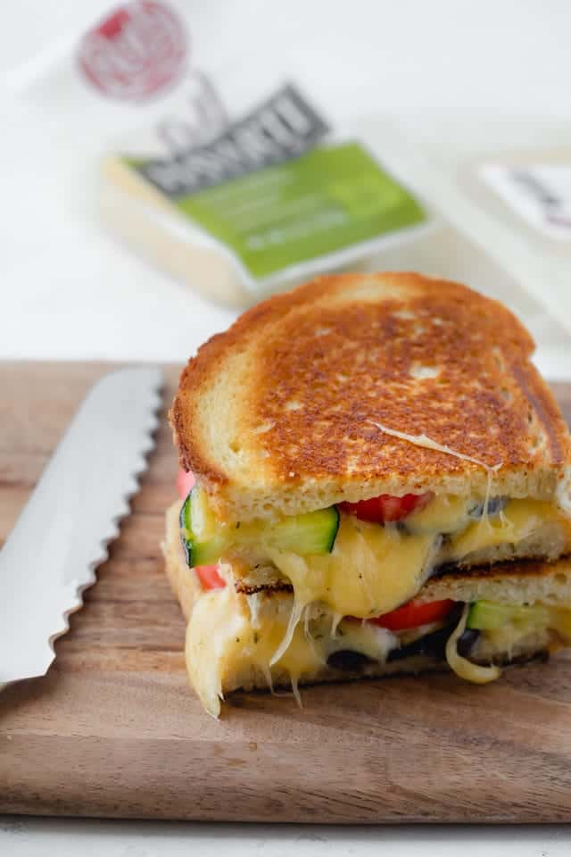 Final roasted vegetable grilled cheese sandwich with a knife nearby