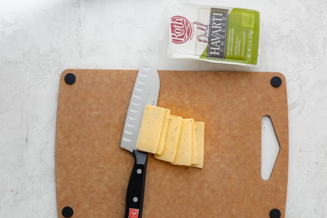 Slicing Havarti cheese on a cutting board