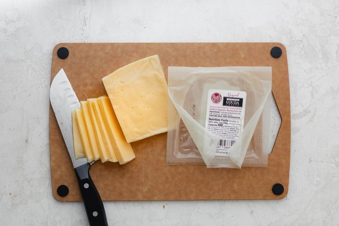 Slicing Gouda cheese on a cutting board