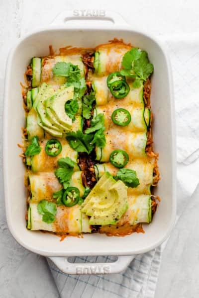 Final zucchini enchiladas garnished with cilantro, jalapenos and avocado