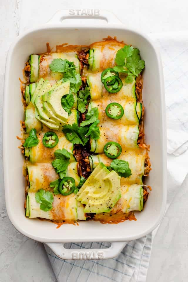 Final zucchini enchiladas garnished with cilantro, jalapenos and avocado