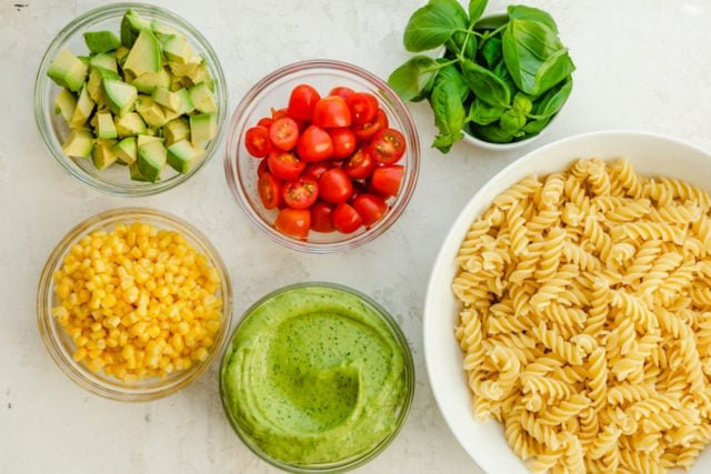 List of ingredients to make the pasta salad including pasta, avocado dressing, corn, avocados, tomatoes and basil