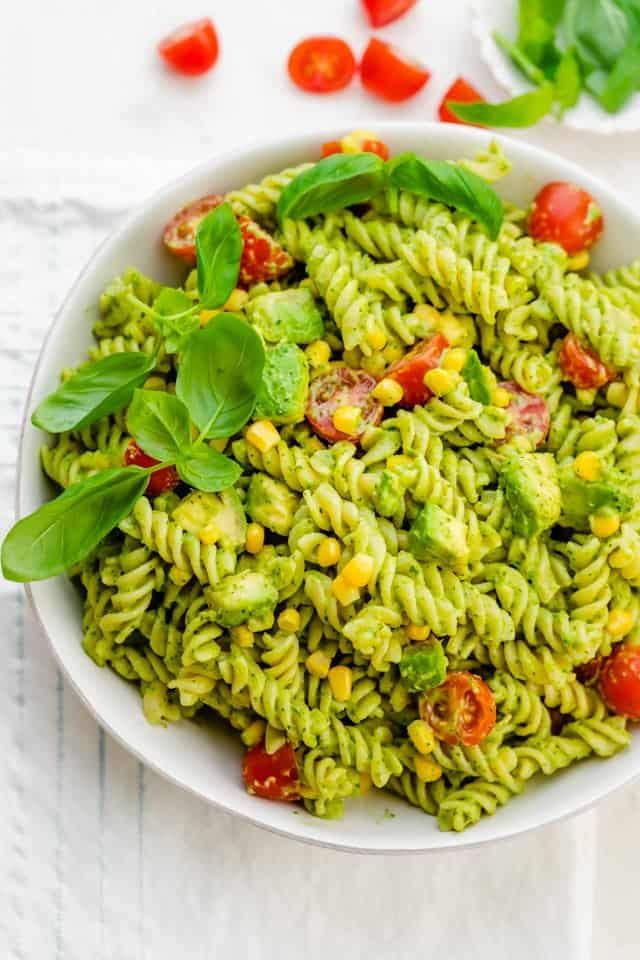 Final bowl of avocado pasta salad dressed and garnished with basil