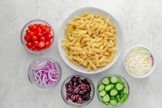 Ingredients to make the recipe: pasta, tomatoes, onions, olives, cucumbers and feta cheese