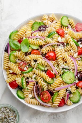 Final Greek Pasta Salad recipe in a large bowl with cucumbers, tomatoes, onions, olives and feta cheese