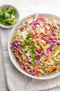 Healthy Coleslaw in a large bowl on a white napkin with green onions on the side