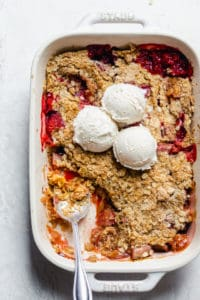 Final rhubarb crisp with scoop taken out and ice cream scoops on top of baking dish