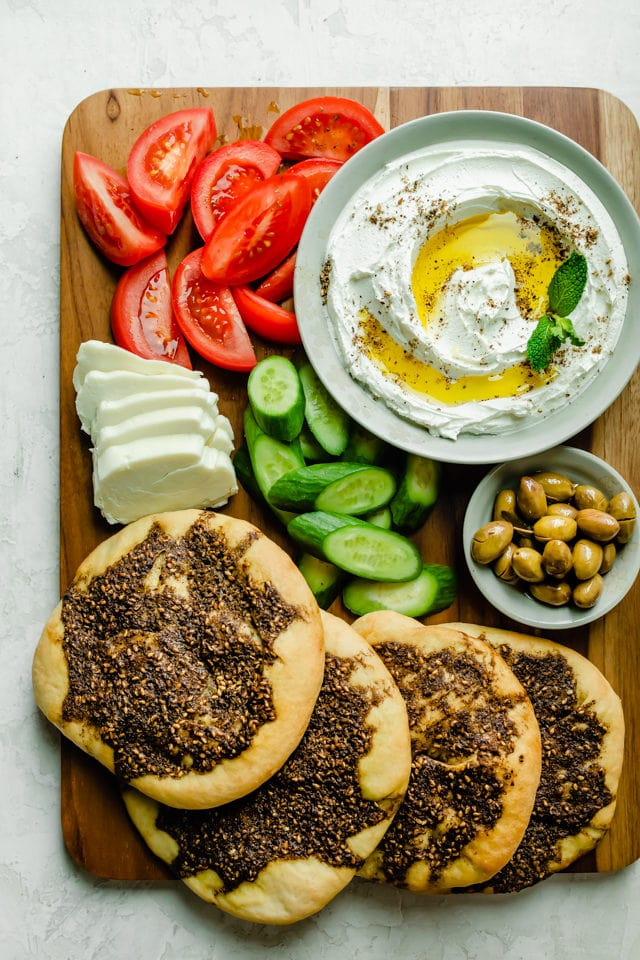 Serving baord with zaatar manakeesh, labneh, olive and vegetables