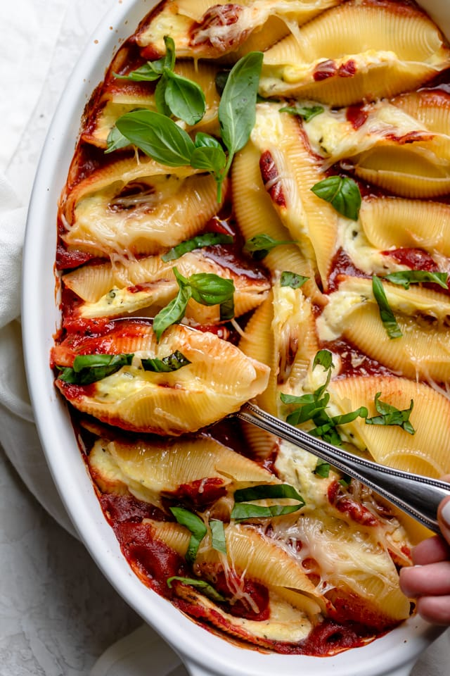 Close up shot of the cheese stuffed shells topped with basil