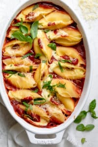 Cheese stuffed shells in a white oval baking dish topped with fresh basil