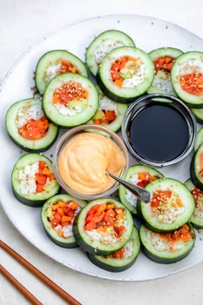Large plate showing the cucumber rolls sliced into large bite-size pieces and served with soy sauce and spicy mayo