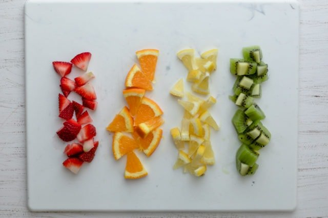 Cut fruits in a row: strawberries, oranges, lemon and kiwi