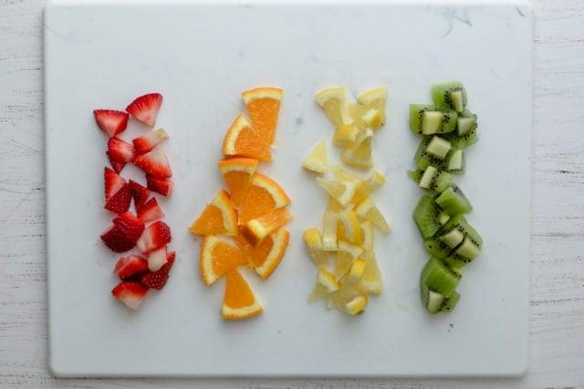Cut fruits in a row: strawberries, oranges, lemon and kiwi
