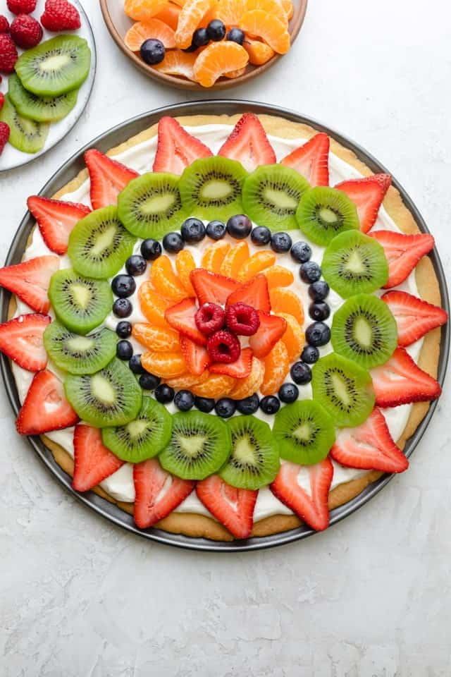 Fruit pizza decorated with strawberries, kiwi, blueberries, clementines and raspberries