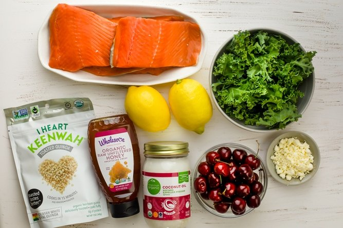 Ingredients to make the recipe including salmon, lemon, honey, coconut oil, along with kale, quinoa, cherries and feta cheese for the salad
