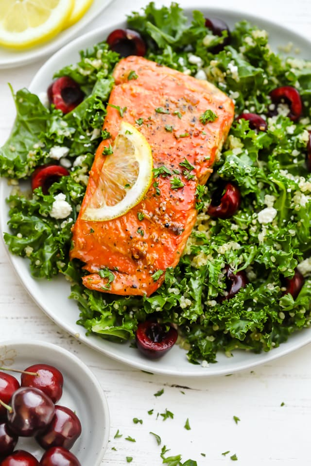Plate of kale quinoa salad topped with honey lemon salmon