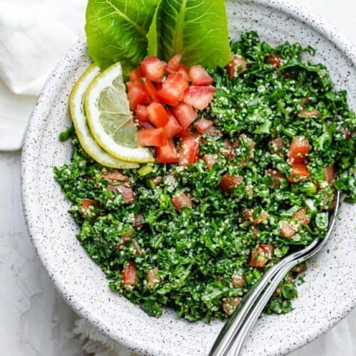Large bowl of kale tabbouleh salad with serving spoons on the inside of the bowl