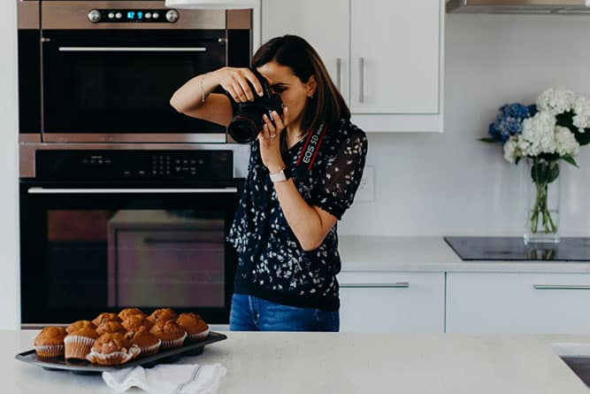 woman taking a photo in a kitchen