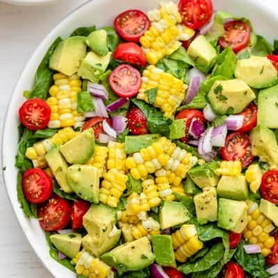 Corn tomato avocado salad in a large white bowl with squeezed limes on the side