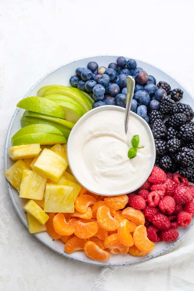 Cream cheese fruit dip surrounded by raspberries, clementines, pineapples, green apples, blueberries and blackberries