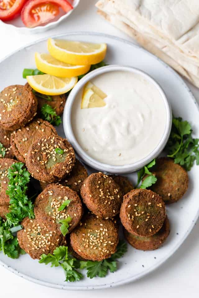 Large platter of Lebanese falafel served with tahini sauce and lemons