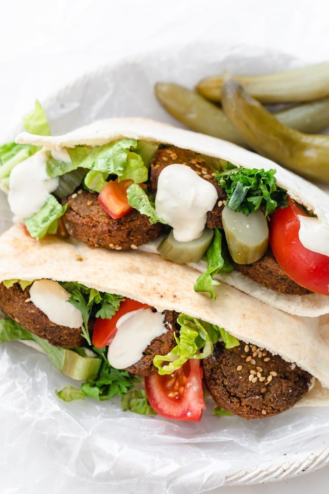 Falafel sandwich made with pickles, tomatoes, parsley and tahini sauce
