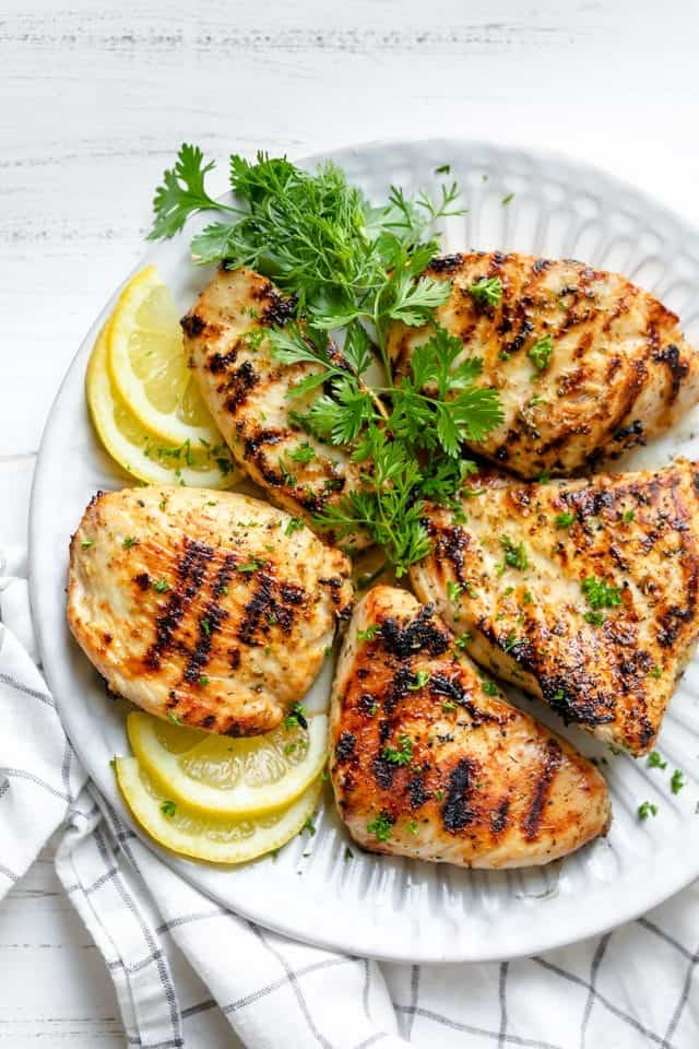 Grilled Lemon Chicken breasts on a plate with lemons and parsley