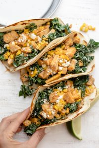 Mexican street tacos with kale, corn and chicken. Hand grabbing one taco