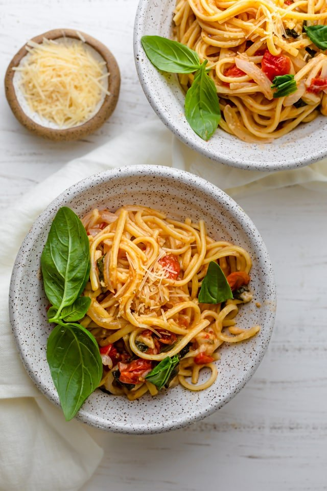 Vegetarian one pan pasta served in two large bowls with a side of parmesan cheese