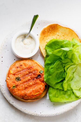 Salmon burgers made with a few ingredients and served with tartar sauce and lettuce