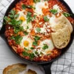 Shakshuka with Feta served with bread and cilantro in a cast iron skillet